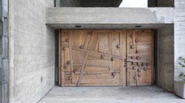 Der Zutritt zur Kirche, die vom bekannten Basler Architketen Hermann Baur entworfen wurde, führt über eine kunstvoll gestaltete Holzpforte. | © Roger Wehrli