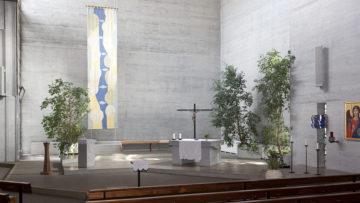 Der Blick in den Altarraum der Kirche: Auffallend ist die Lichtführung sowie der von Ferdinand Gehr gestaltete Wandteppich im Hintergrund. | © Roger Wehrli