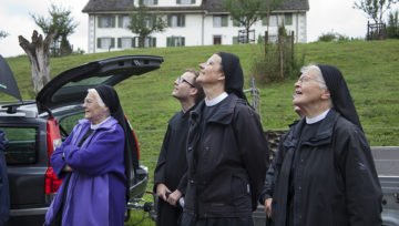 Gespannt verfolgen die Fahrer Schwestern um Priorin Irene Gassmann (Mitte) und Pater Thomas vom Kloster Einsiedeln (Zweiter von links), wie die Turmkugel herabgelassen wird. | © Roger Wehrli