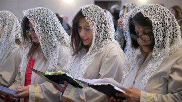 Die Mitglieder des Frauenchors in der vordersten Reihe tragen allesamt beige Gewänder und ein glitzerndes Kopftuch.