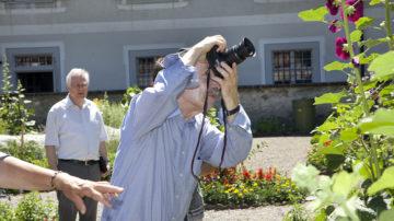 Gartengenuss ist auf vielerlei Weise möglich. Während die einen fachsimpeln oder sich praktische Ratschläge bei Schwester Beatrice holen, halten andere ihre Eindrücke per Kamera fest und üben sich in der Pflanzenfotografie. | © Roger Wehrli