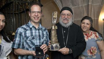 Diakon und Gemeindeleiter Marcus Hüttner mit Father Rewis und dem kostbaren Arm-Reliquiar aus dem Münsterschatz. | © Roger Wehrli