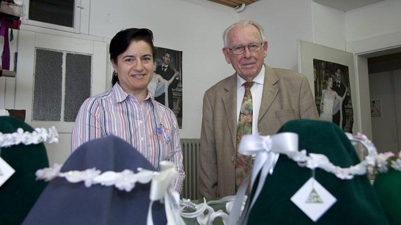 Maria D'Arino und Marcel Geissman, die Mitarbeiterin und der Geschäftsführer der G. Geissmann-Huber AG in Hägglingen, inmitten ihres umfangreichen Sortiments an Erstkommunionkränzen. | © Roger Wehrli
