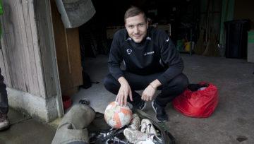 Jonas Burch vor einem Sack mit gespendetem Fussball-Equipment. Der angehende Lehrer hilft Felix Häuser bei der Organisation und Durchführung der Fussballtrainings. | © Roger Wehrli