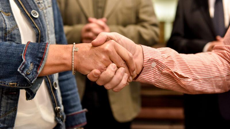 Gottesdienstbesucher geben sich  in der Kirche die Hände zum Friedensgruss - Bis auf Weiteres nicht mehr wegen Ansteckungsgefahr. | © kna-bild