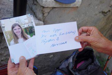 Eine Pilgerin trägt das Bild ihrer Enkelin mit, die auf einem Zettel ihren Wunsch nach der ersten weiblichen Päpstin notiert hat. | © Vera Rüttimann