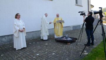 Während Pfarrer Baumgartner, rechts, und Pfarrer Hübscher die Osterkerze entzünden, wartet Anita Kohler auf ihren nächsten Einsatz als Gebärdendolmetscherin. | © Werner Rolli