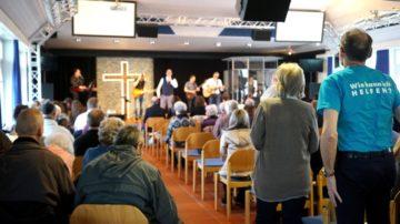 Sonntagsgottesdienst im Gemeindezentrum «Bethel» der Pfingstgemeinde in Wettingen: Vorne im Chorraum spielt eine junge Band, flankiert von einem grossen illuminierten Kreuz.   © Vera Rüttimann