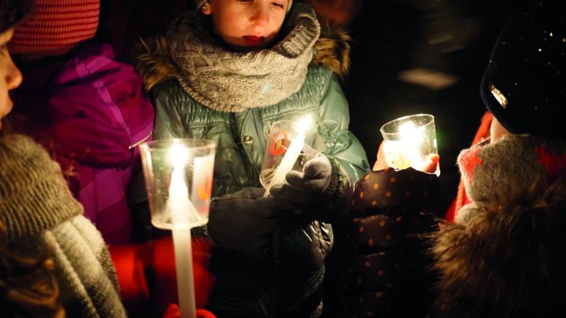 Kinder geben einander das Friedenslicht weiter.   © Verein Friedenslicht Schweiz
