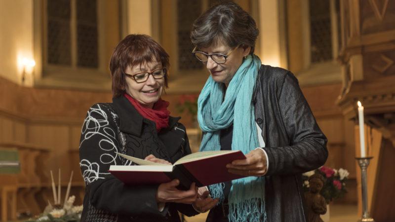 Zu Maria gehört auch das Buch. Elsbeth Frey (links) übergibt das Buch, in das die Herbergsmütter und -väter ihre Erlebnisse mit Maria hineinschreiben können, an Margrit Muoth. | © Werner Rolli