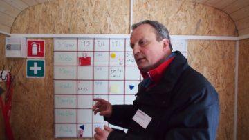 Im Inneren des Caritas-Wagens erklärt Projektleiter Andy Huwyler die Arbeit seines Teams. Im Hintergrund der Einsatzplan. | © Andreas C. Müller