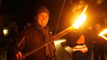 Simon Hohler hat die Fackeln entzündet. Nun geht's mit der Gruppe hinab in die Ranftschlucht zur Andacht. | © Vera Rüttimann