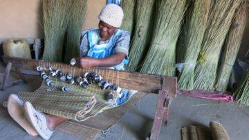Alta Dludla knüpft Strohmatten. Dieser Erwerb ermöglicht es ihr, Vieh zuzukaufen.   © Patricio Frei.