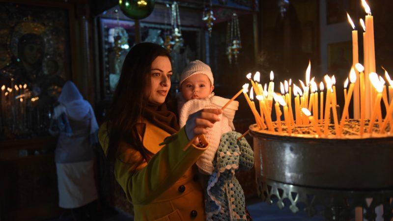 Angelus Silesius formulierte: «Und wäre Christus tausendmal in Betlehem geboren und nicht in dir, du wärest ewiglich verloren.» Das Bild zeigt eine junge Frau aus Palästina, die mit ihrem Baby auf dem Arm in der Geburtskirche Jesu Christi in Bethlehem Kerzen am Kerzenaltar anzündet. | Foto © kna-bild