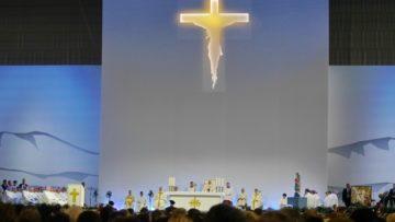 Auf grosser Bühne unter einem riesigen Kreuz steht der Sitz von Papst Franzsikus. Über Leinwände wird alles in die hinteren Teile der Palexpohalle übertragen. | © Anne Burgmer