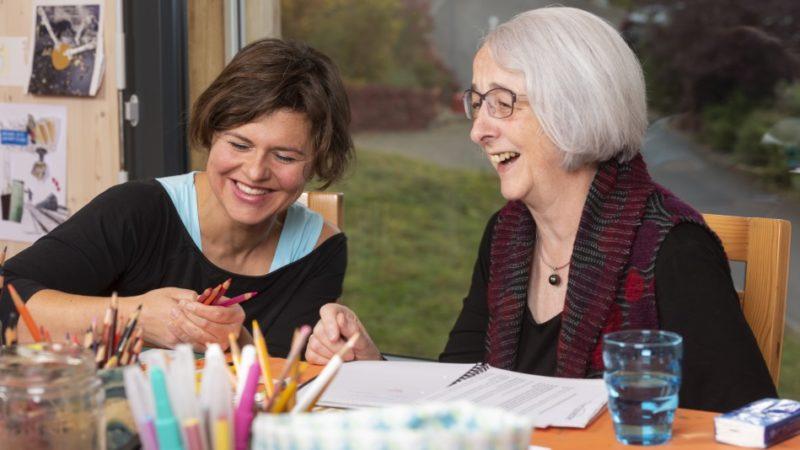 Jacqueline Fahrni (links) und Klara Fricker bei der Künstlerinnen-Stabsübergabe. Angeregt unterhalten sich die beiden Frauen über Techniken, Symbolik in Bildern und ihr jeweiliges künstlerisches Schaffen. | © Werner Rolli