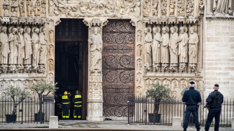 Zwei Feuerwehrmänner stehen an einer geöffneten Tür des Hauptportals der gelöschten Kathedrale Notre-Dame am 16. April 2019 in Paris und schauen in die Kirche. | © kna-bild