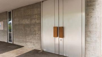 Wer sich bei Kirchen kunstvoll verzierte Holztüren gewohnt ist, wundert sich über die Aluminiumtüren der Heilig Geist-Kirche in Suhr. In Anlehnung an den industriellen Werkstoff Beton wurde Aluminium als Baustoff für die Türen gewählt. | © Werner Rolli