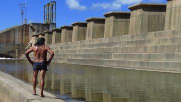 Ein Indigener vor einem Staudamm im Amazonasgebiet. Die Regierung unter Präsident Jair Bolsonaro hat das Ziel, die Indigenen im Amazonasgebiet in die industrialisierte Gesellschaft zu integrieren. | © Stefan Salzmann, Fastenopfer